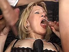Blonde mature gets facial from two cocks in group