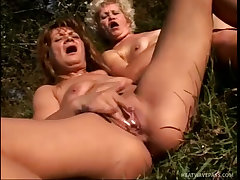 Old broads masturbate together outdoors